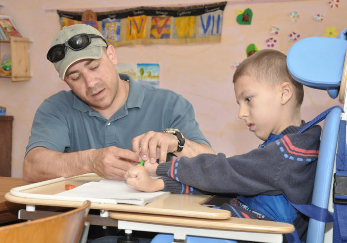 Master Sgt. Jeff Villemarette helps a boy with cerebral palsy color during a special education class April 27, 2010, at the Nadjeshda Children's Center in Kyrgyzstan. Nadjeshda is home for 60 children and teenagers who are disabled in different ways. Sergeant Villemarette is assigned to the Transit Center at Manas. (U.S. Air Force photo/Staff Sgt. Carolyn Viss)