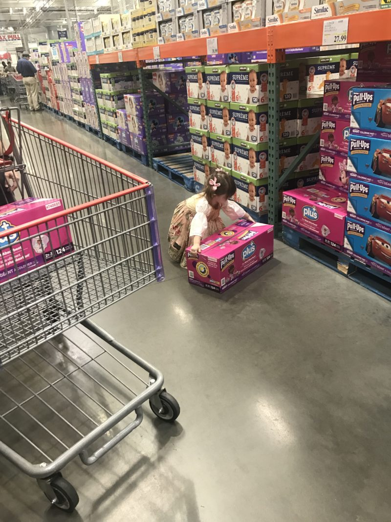 little girl picking up pull ups plus box costco